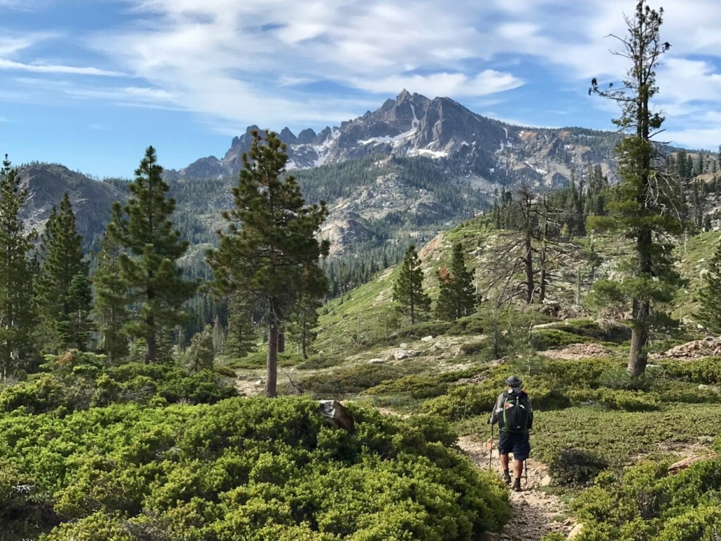 A hiker approaches the dramatic Sierra Buttes (8,857 feet in elevation) on the Pacific Crest Trail in the northern reaches of the Sierra Nevada.