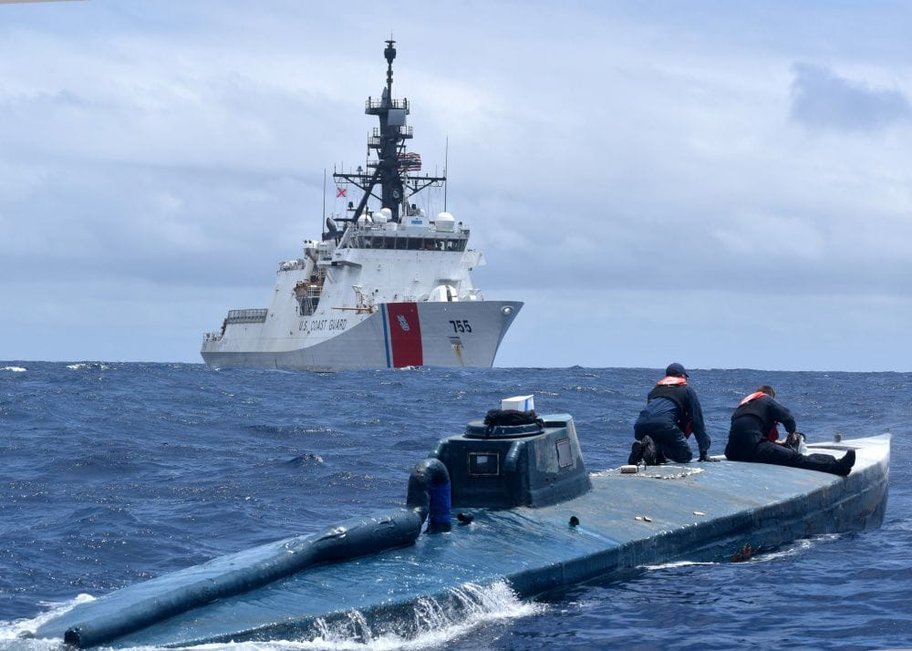 Coast Guardsmen boarding suspected drug smuggling vessel