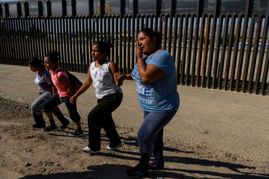 After crossing the Rio Grande from Mexico into the United States, Karla Yadira Rivera, 36, cries as she walks to Border Patrol agents with her daughters Karla, 11, Andrea, 12, and Emilia, 17, in El Paso, Texas, on June 13.