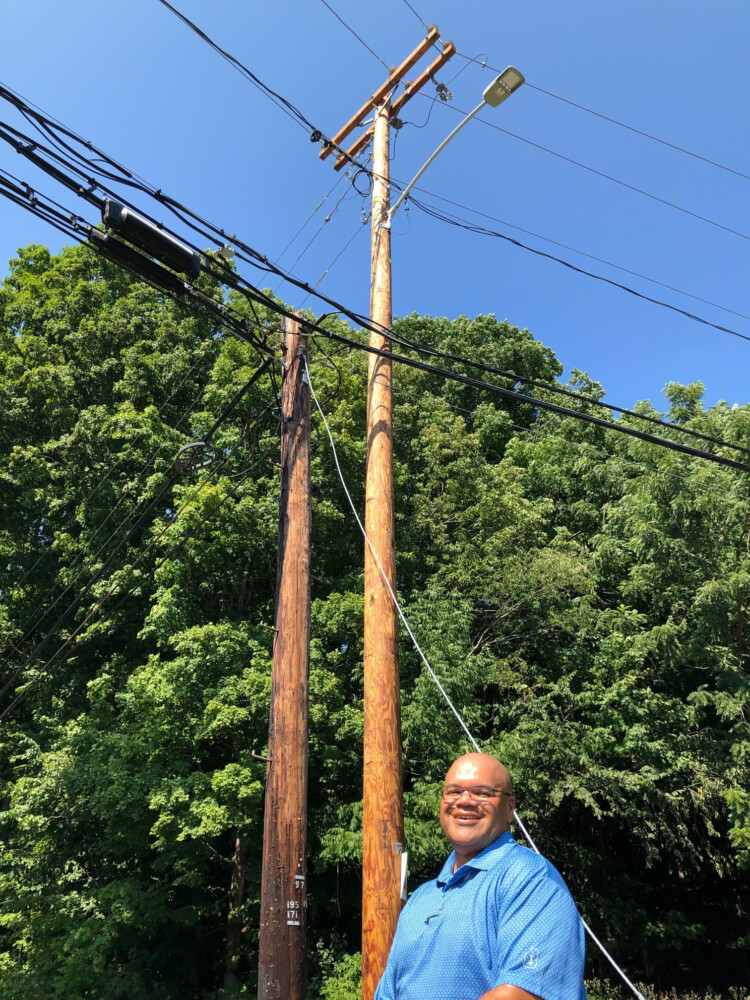Lloyd Hendrix, who's overseeing Central Maine Power's plan to harden its electric grid against storm and tree damage, shows the contrast between an older, thinner utility pole and the taller, stronger version that replaced it along Route 101 in Eliot. The circuit here has among the worst records for power outages in CMP's system, and is targeted for an upgrade this fall as part of a 10-year, network-wide proposal.