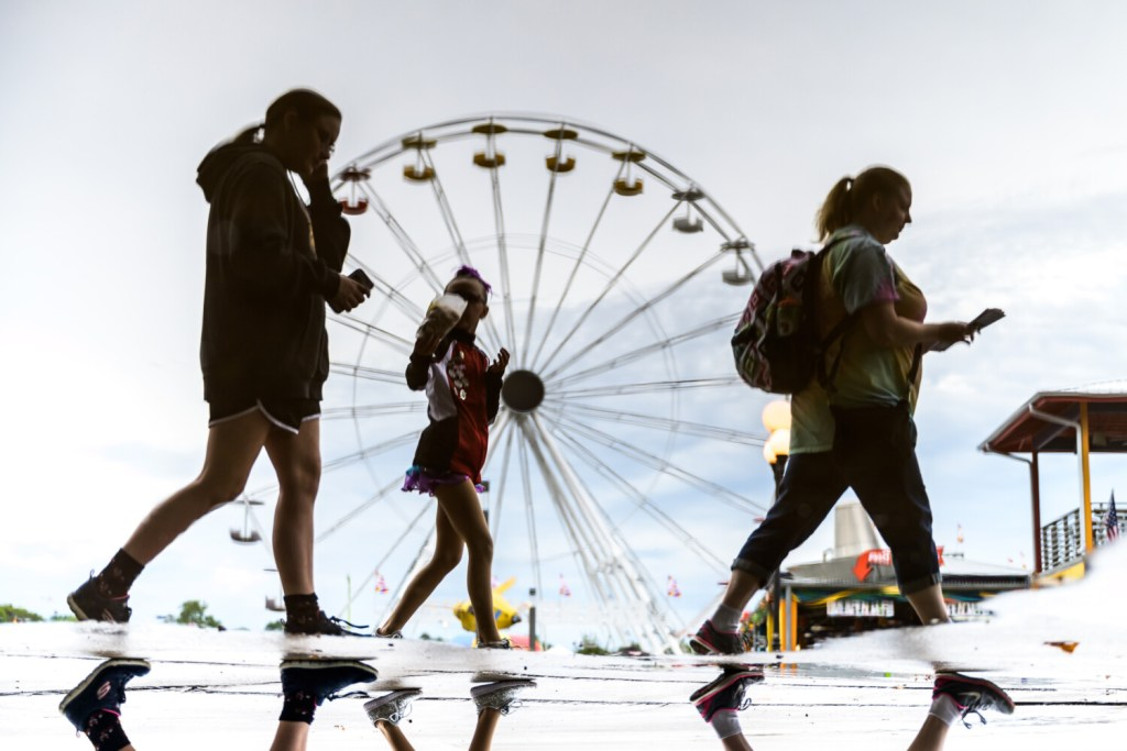 Visitors trek through the Iowa State Fair during rainy conditions Aug. 12 in Des Moines.