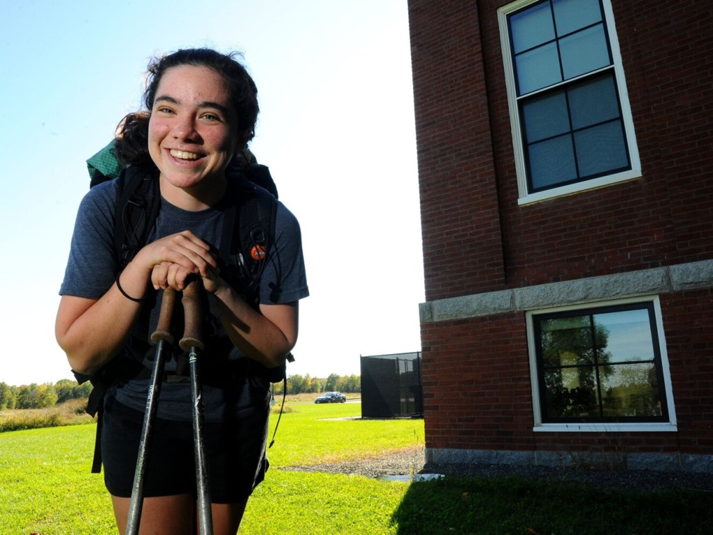 Kaylin Brown, a graduate of the Maine Academy of Natural Sciences, is pictured back on campus in Hinckley on Sunday. Brown, who is seen with her trekking poles and her backpack, returned Saturday after finishing the 2192-mile Appalachian Trail from Georgia to Maine.