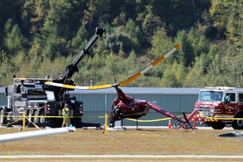 Emergency crews use a tow cable to turn a crashed helicopter upright on Saturday at Sanford Seacoast Regional Airport.