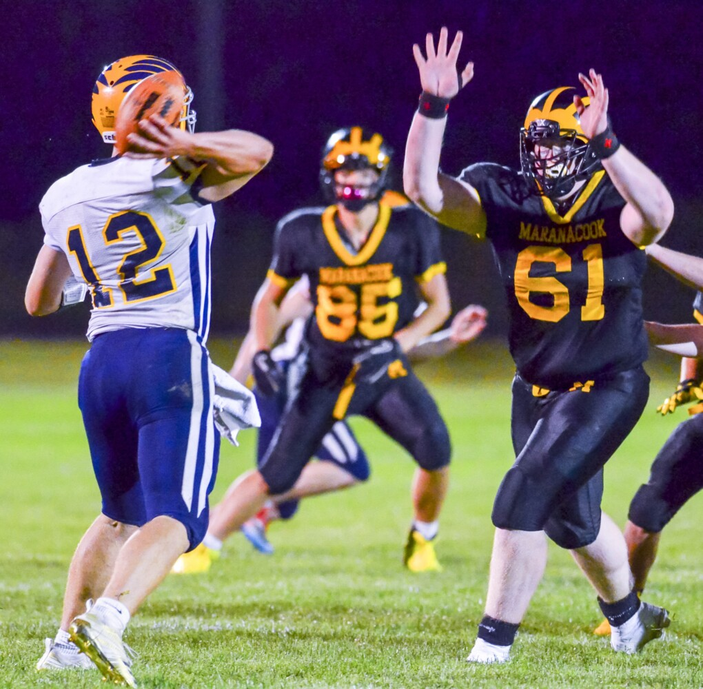 Boothbay quarterback Hunter Crocker, left, passes under pressure from Maranacook's Ashael Plum during a game at the Ricky Gibson Field of Dreams on earlier this season in Readfield.