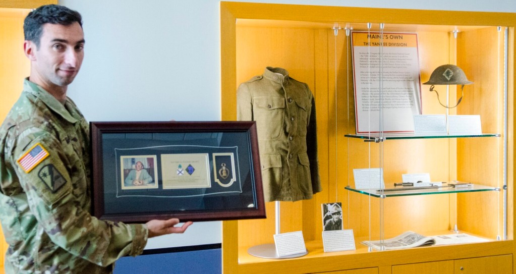 Capt. Jonathan Bratten holds the framed Purple Heart of Sgt. Erroll Wilbert Brawn near where it will be displayed, next to a case of World War I items at Camp Chamberlain in Augusta. A presentation was made Thursday by the nonprofit Purple Hearts Reunited.