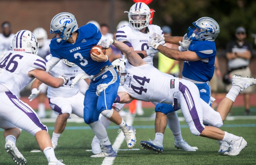 Colby College quarterback Matt Hersch scrambles for a short gain as he is tackled by Amherst's Joe Kelly on Saturday at Colby College in Waterville.