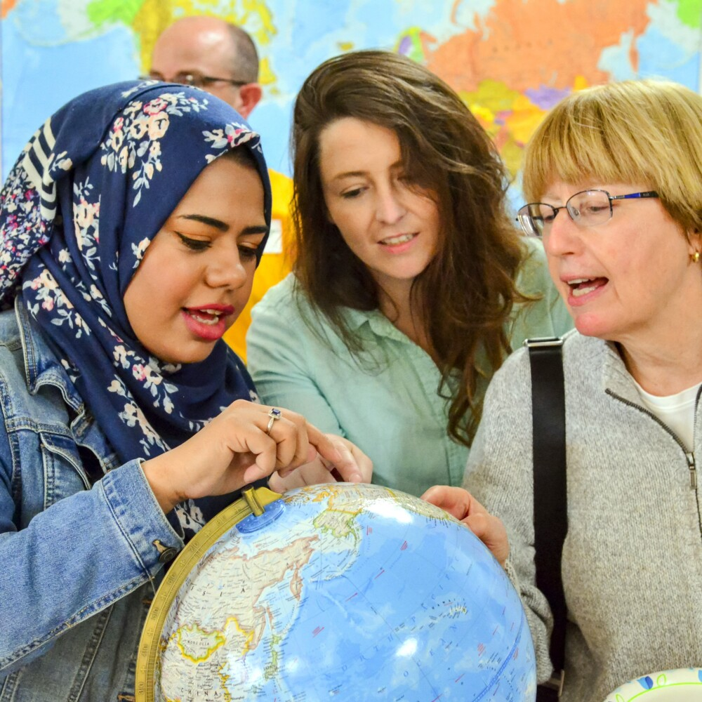 Hadeel Alsaleh, left, Melissa Taylor and Deb Sewall chat around a globe during the open house reception Sept. 18 at the new Augusta Multicultural Center at 70 State St., next to Lithgow Library, in Augusta.