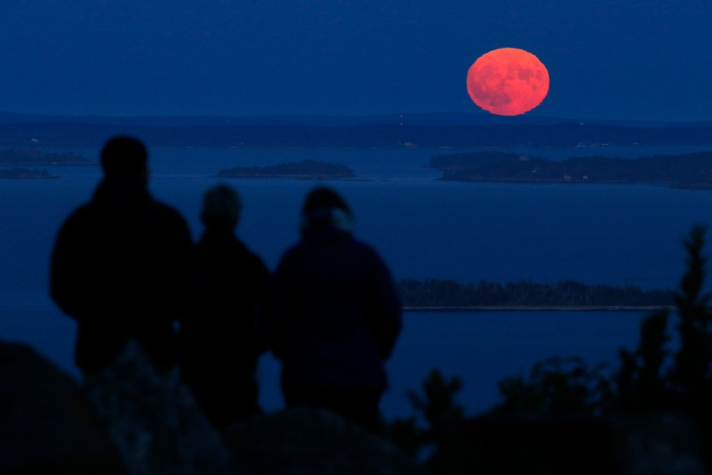 Jack and Kathy Duepree, of Camden, left and center, and their friend Betsy Starman, of Naples, Fla., watch the nearly-full harvest moon rise over Penobscot Bay on Sept. 13 from the summit of Mt. Battie in Camden. Fall is upon us and southern Maine had its first widespread frost on Thursday.