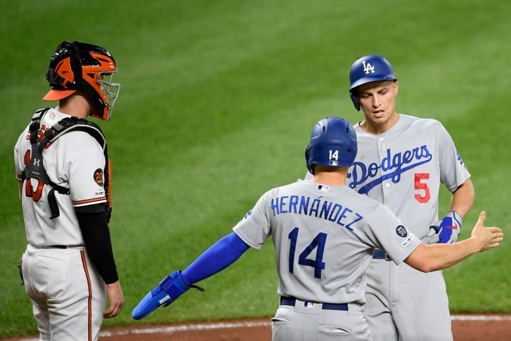 Corey Seager, right, celebrates his two-run home run with Enrique Hernandez during the third inning of the Dodgers' 7-3 win over the Orioles in Baltimore. The Dodgers clinched their seventh straight NL West title with the win.