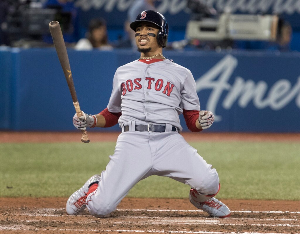 Boston Mookie Betts drops to his knees after avoiding being hit by a pitch Tuesday night against the Blue Jays in Toronto. Betts hit a leadoff home run, but Boston lost, 4-3.