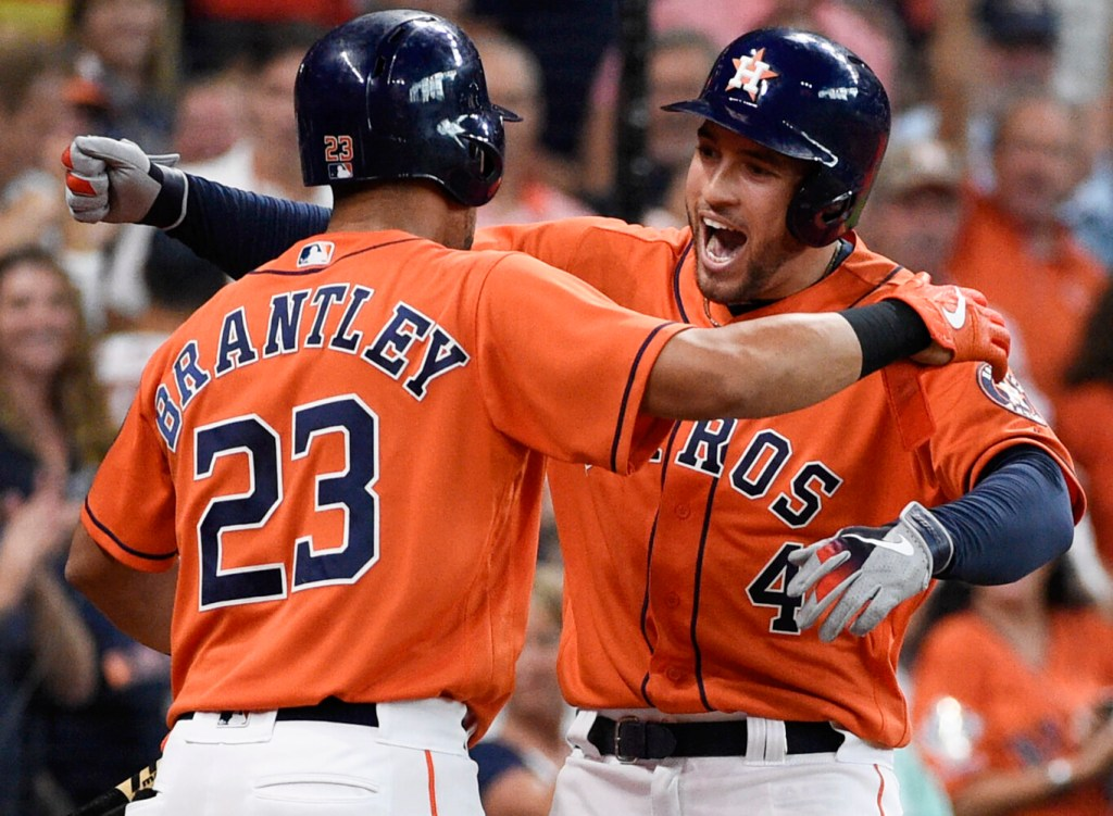 Houston's George Springer, right, celebrates one of his three homers with Michael Brantley during the Astros' 13-5 win that clinched the AL Central, in Houston.
