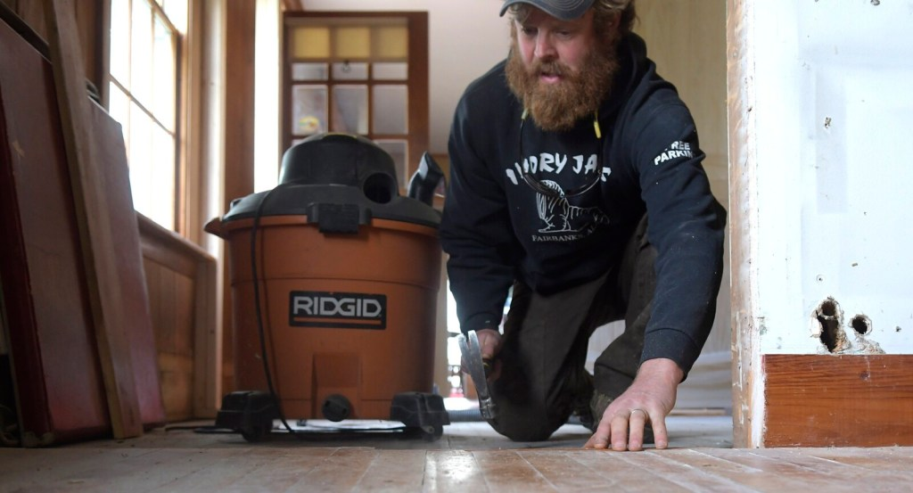 "Chase Morrill pounds a nail Thursday into the floor of the farmhouse his family recently purchased in Manchester. The stars of ""Maine Cabin Masters"" are opening Kennebec Cabin Company, a retail and event facility at the location."