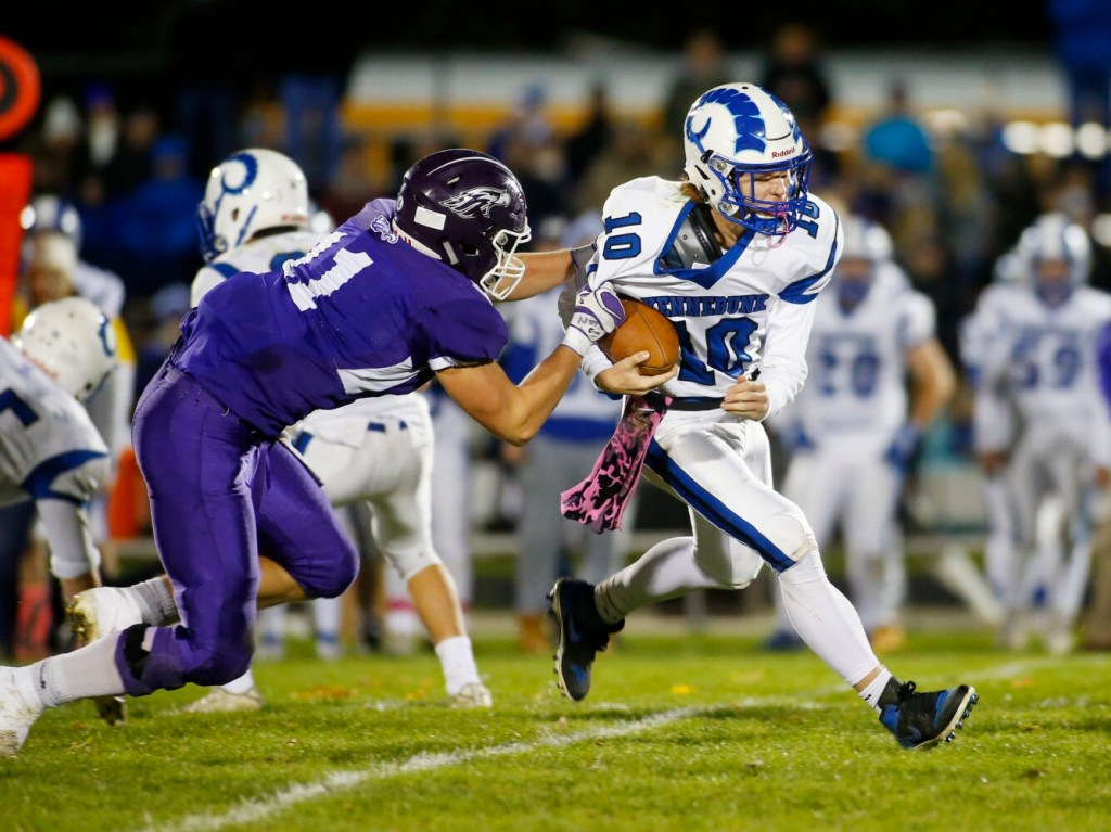 Connor Caverly of Marshwood grabs Tommy Lazos of Kennebunk during the Rams' 48-14 win Friday in South Berwick.
