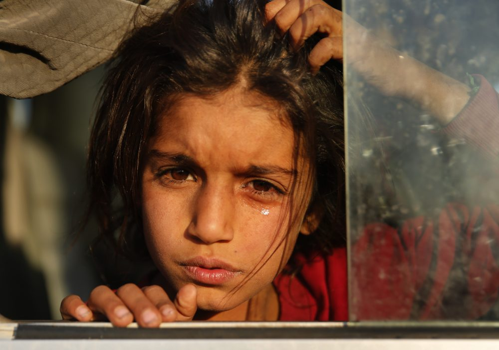 A Syrian girl who is newly displaced by the Turkish military operation in northeastern Syria weeps as she sits in a bus upon her arrival at the Bardarash camp, north of Mosul, Iraq, on Wednesday. The camp used to host Iraqis displaced from Mosul during the fight against the Islamic State group and was closed two years ago. The U.N. says about 160,000 Syrians have been displaced since the Turkish operation started last week, most of them internally in Syria.