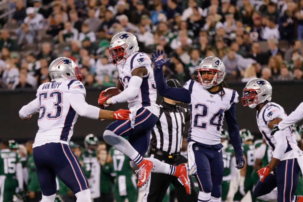 New England Patriots free safety Devin McCourty celebrates with teammates Kyle Van Noy, 53, and Stephon Gilmore after intercepting a pass during the Patriots' win over the Jets on Monday in East Rutherford, N.J.