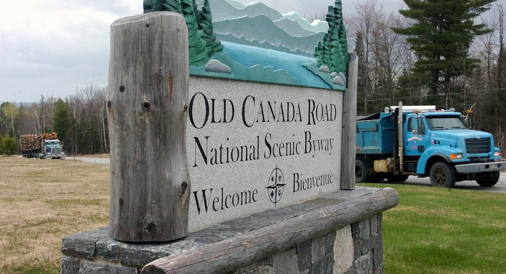 Staff photo by David Leaming WELCOME: Loaded pulp trucks pass a large sign marking the site of a the Old Canada Road scenic byway property off US Route 201 in Solon.