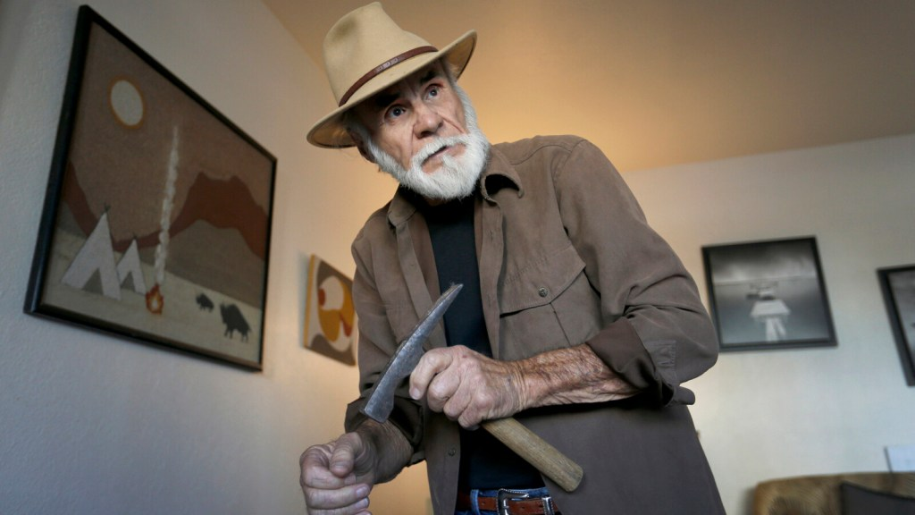 Field paleontologist Richard Cerutti, shown in his Imperial Beach apartment, holds a brick hammer that he uses to help loosen hardened sediment at some excavations.