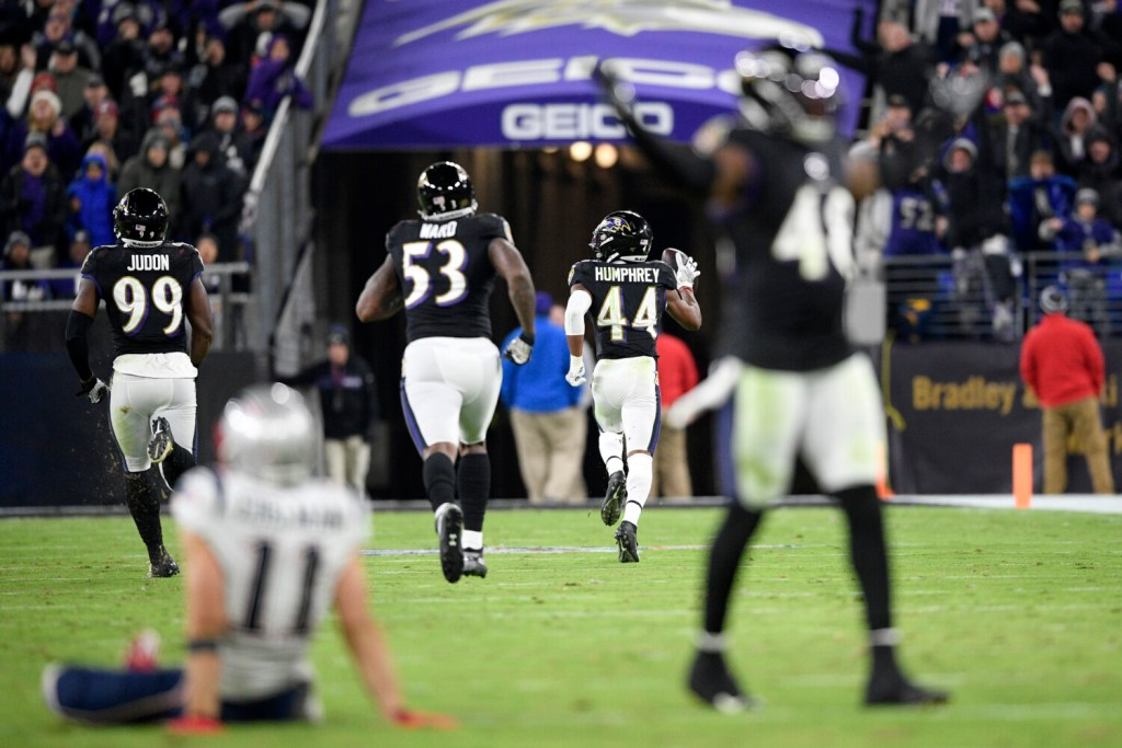 Baltimore Ravens cornerback Marlon Humphrey runs for a touchdown after recovering a fumble by New England wide receiver Julian Edelman on Sunday night in Baltimore.