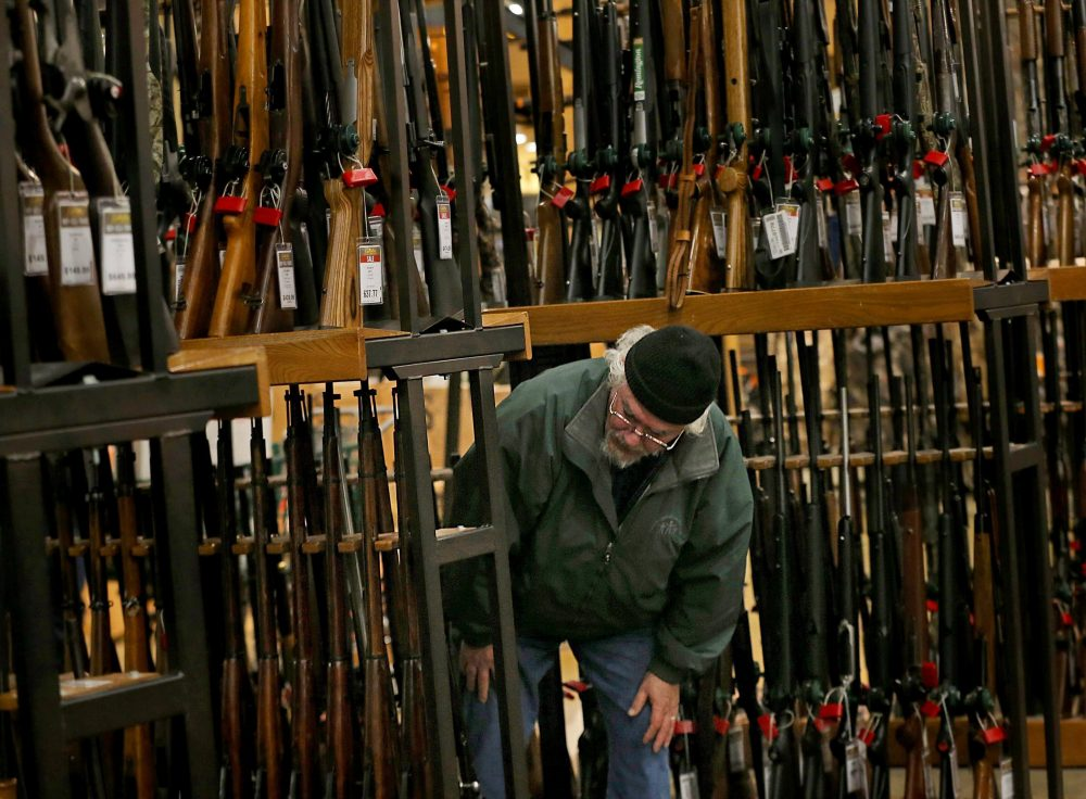 A man looks at the shotgun section of Cabela's while shopping on Black Friday in Hazelwood, Mo. The number of background checks conducted by federal authorities is on pace to break a record by the end of this year.