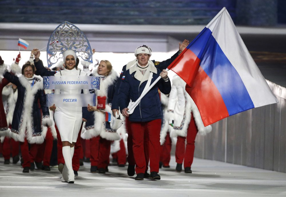 Alexander Zubkov of Russia carries the national flag as he leads the team during the opening ceremony of the 2014 Winter Olympics in Sochi, Russia. The Russian flag and anthem have been banned from international competition for four years by an anti-doping agency.
