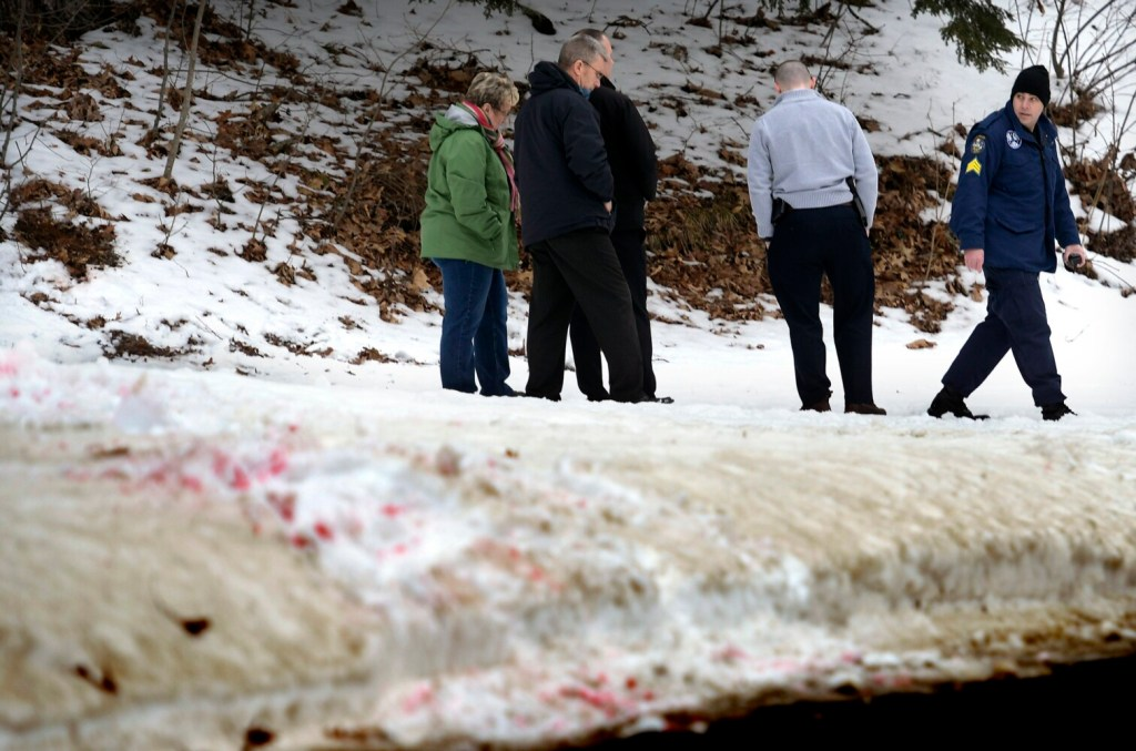 Maine State Police detectives escort  Assistant Attorney General Meg Elam along a blood trail from a shooting and stabbing that occurred in the early hours of Saturday in Gardiner.