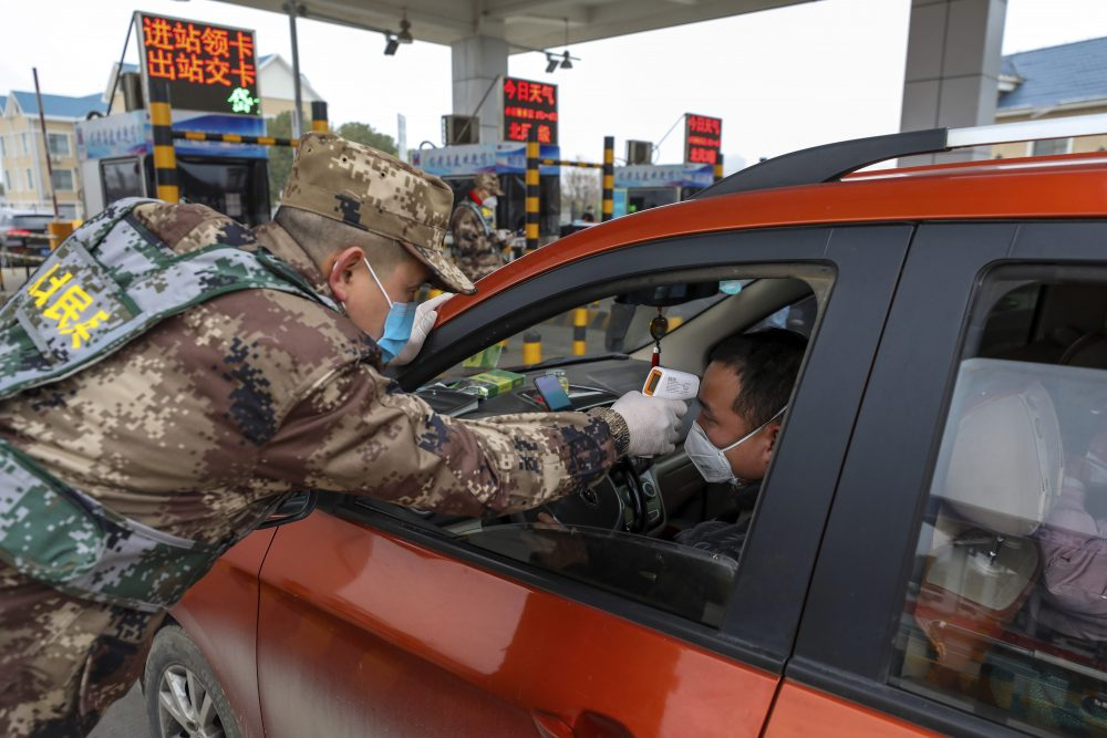A militia member uses a digital thermometer to take a driver's temperature at a checkpoint at a highway toll gate in Wuhan in central China's Hubei Province, Thursday.