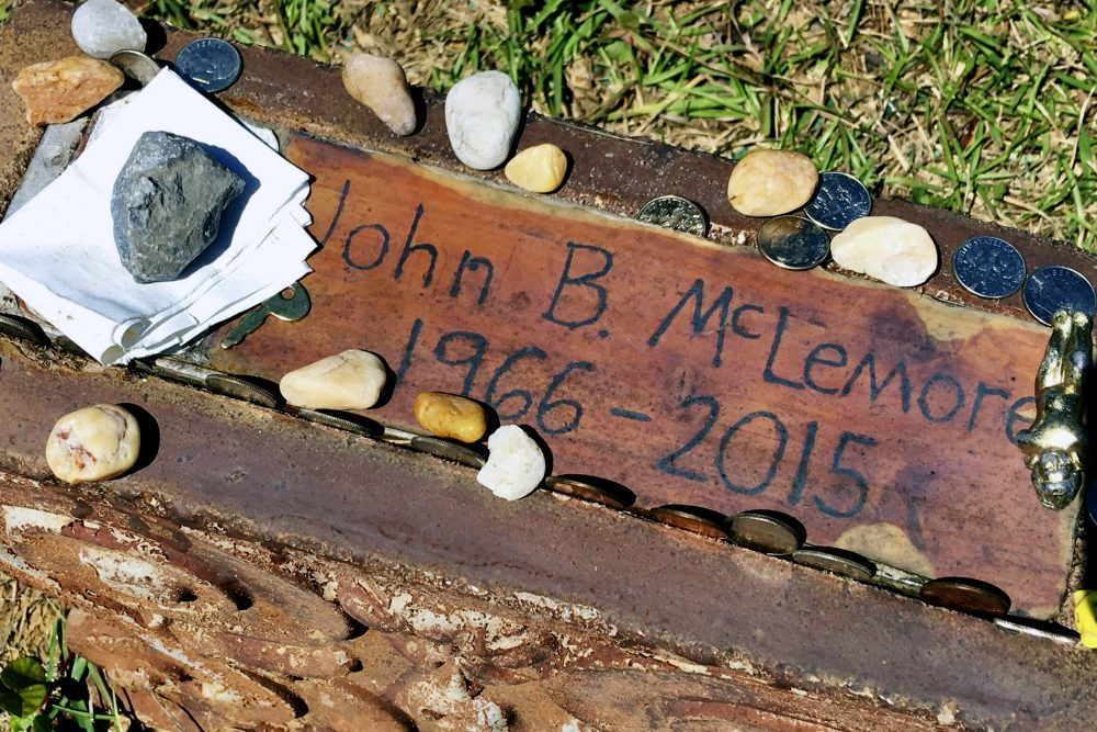 """This May 3, 2017, file photo, shows the grave of John B. McLemore in Green Pond, Ala., who is featured in the serialized podcast """"S-Town."""" WIAT-TV reported that lawyers for the estate of McLemore, the key character in """"S-Town,"""" and attorneys for the producer have selected a mediator to work on a settlement."""