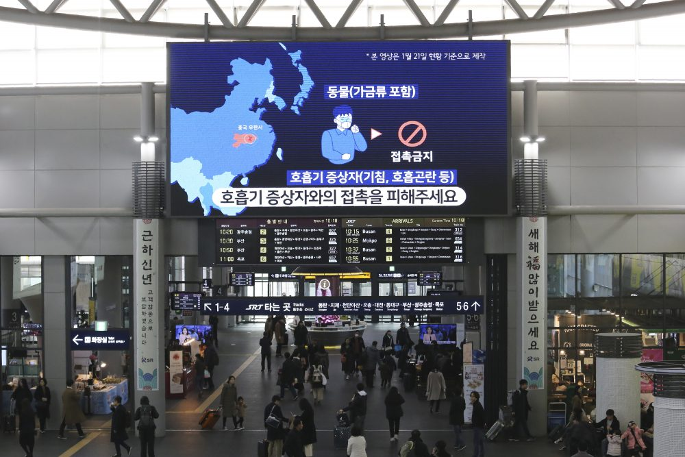 People walk under a screen warning about a new coronavirus at Suseo Station in Seoul, South Korea, Friday, Jan. 24.