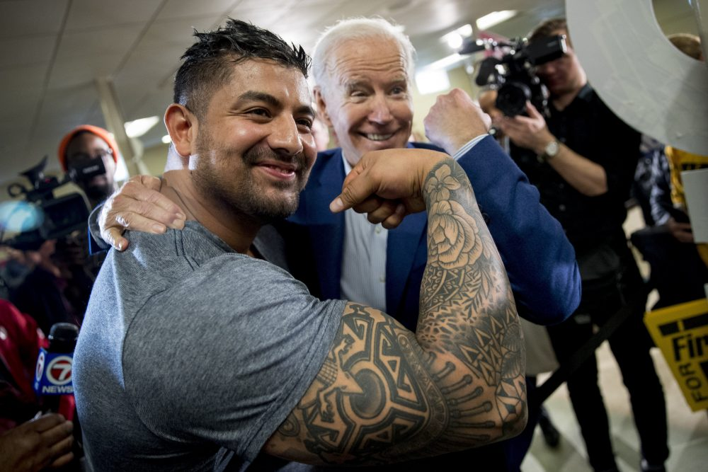 Democratic presidential candidate Joe Biden flexes his arm along with Jaime Karnilaw of Concord, N.H., as they pose for a photograph Monday at a campaign stop in Gilford, N.H. Biden sought to lower expectations for his performance in Tuesday's primary.