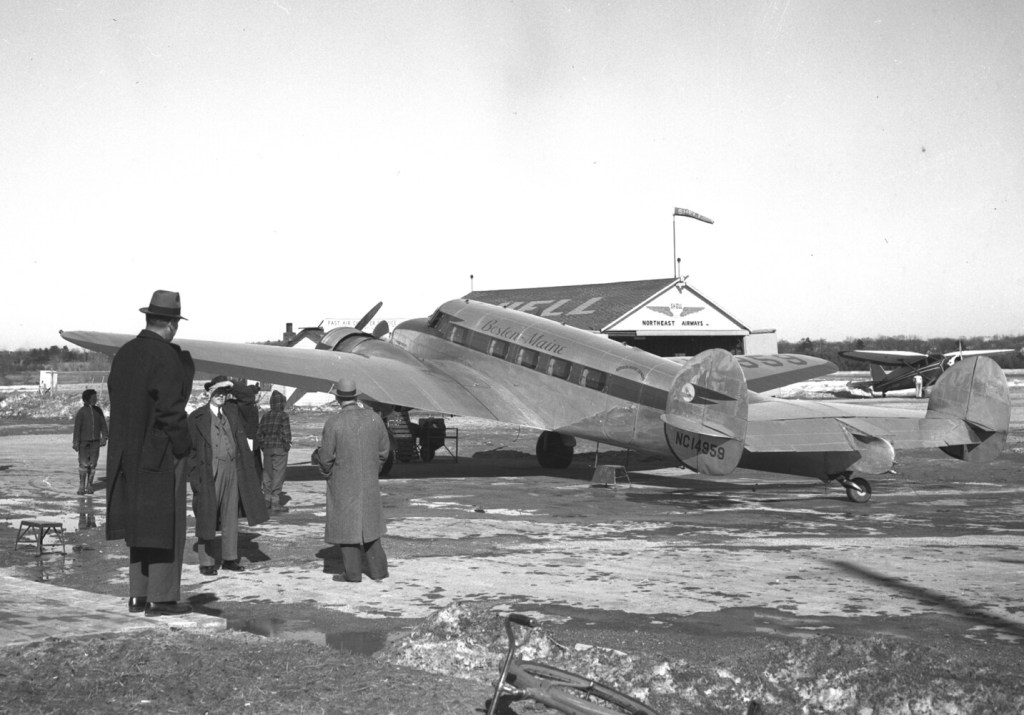 A Boston-Maine airplane at the Portland Municipal Airport in 1941. The hanger in the background shows the company's new name as of 1940: Northeast Airlines in 1940 and eventually Delta Airlines.