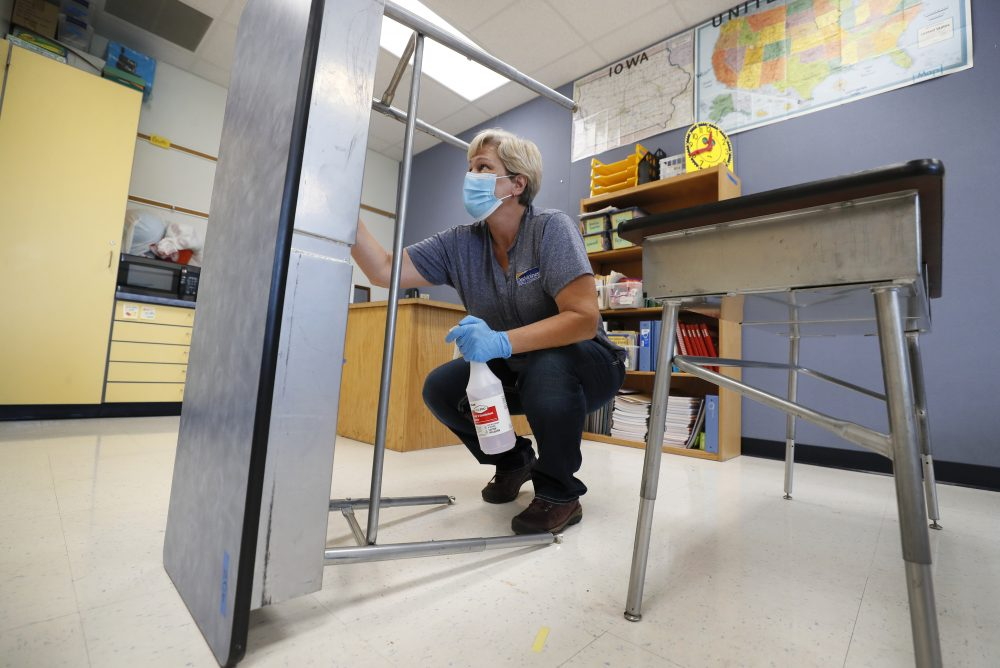 Des Moines Public Schools custodian Cynthia Adams cleans a desk in a classroom at Brubaker Elementary School, Wednesday in Des Moines, Iowa.