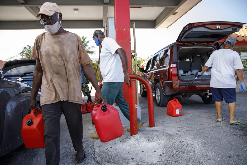 A resident walks with containers filled with gasoline at Cooper's gas station before the arrival of Hurricane Isaias in Freeport, Grand Bahama.