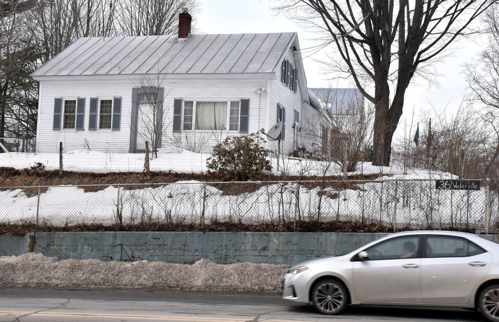 A motorist passes the home at 36 Waterville Road in Skowhegan, where police and state animal welfare agents searched as part of an animal abuse investigation on Wednesday.