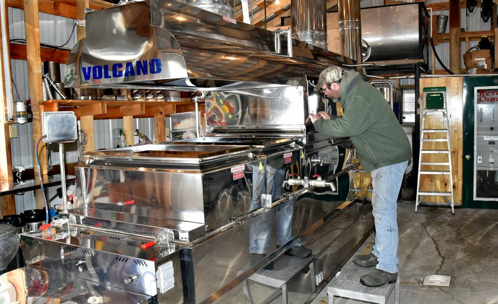 Maple syrup producer Jim Smith peers into his evaporator Tuesday in preparation for another boil at his Smith Brothers Maple Syrup Products operation in Skowhegan. Smith said the sap was running and he made 60 gallons of syrup last Sunday. He is taking part in the annual Skowhegan Maple Fest, which begins this Friday and runs through Sunday, which is Maine Maple Sunday.