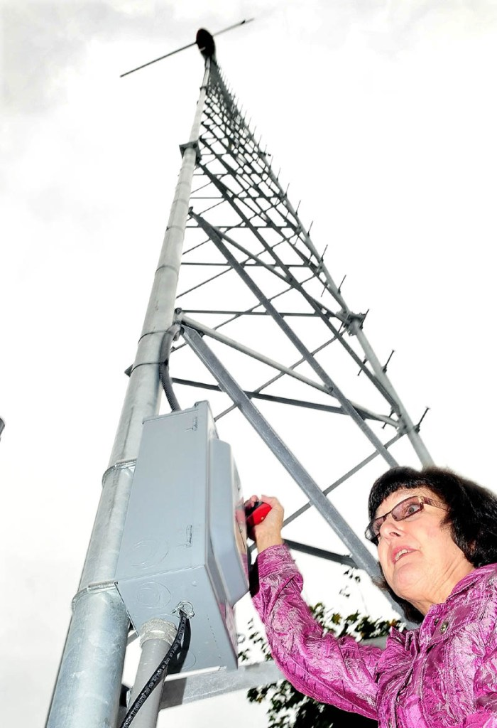 POWER UP: Kennebec Valley Community College President Barbara Woodlee throws the switch to the new wind turbine during a ceremony at the Fairfield school on Wednesday. The turbine will power the nearby Muriel P. Frye building and become a teaching tool for students.