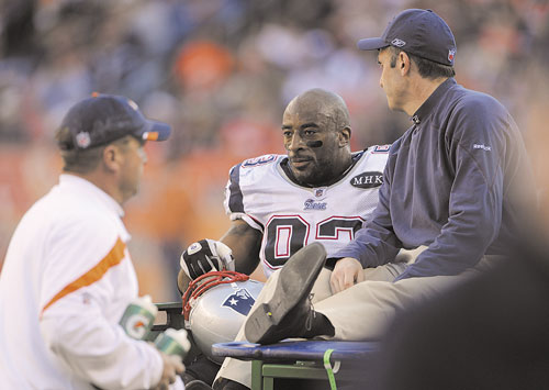 CARTED OFF: New England Patriots defensive end Andre Carter is carted off the field after an injury in the second quarter against the Denver Broncos on Sunday in Denver.