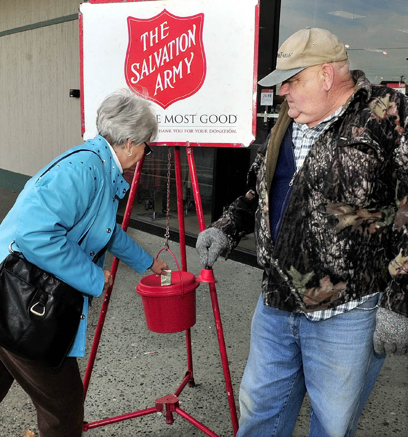 SALVATION: Salvation Army bellringer Donald Peace watches as Joyce St Pierre donates in front of the J.C. Penney store in Waterville on Tuesday. Maj. Karin Dickson said the Waterville organization has only reached a portion of its goal this year to fund services and is anxious for more volunteer bellringers for the annual holiday Kettle campaign.