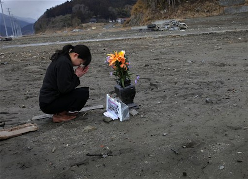 Mika Hashikai, 37, mourns for her mother and father, victims of the March 11, 2011 earthquake and tsunami, in Rikuzentakata, Iwate Prefecture, northeastern Japan on Sunday, March 11, 2012. On Sunday, Japan marks the one-year anniversary of the March 11 earthquake and tsunami that triggered a nuclear crisis.(AP Photo/Itsuo Inouye)