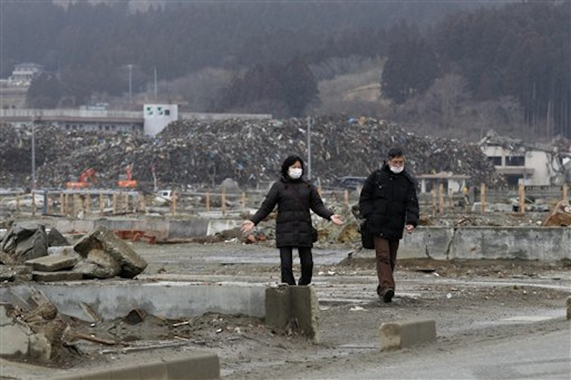 A couple walk in an area devastated by the March 11, 2011 earthquake and tsunami, in Minamisanriku, Miyagi Prefecture om Sunday, March 11, 2012. Japan was remembering the terrifying earthquake and tsunami that struck the nation a year ago on Sunday, killing just over 19,000 people and unleashing the world's worst nuclear crisis in a quarter century. (AP Photo/Shizuo Kambayashi)