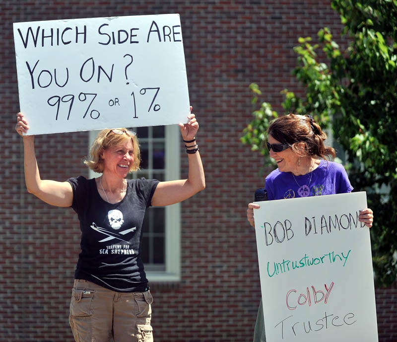 PROTEST: Kim Cormier, left, of Benton, and Lucia Robinson, of Whitefield, stand outside the Diamond Building at Colby College on Mayflower Hill Drive calling for chairman of College's Board of Trustees Robert E. Diamond Jr. to resign from the Colby board of trustees and for Colby for remove him from their board and give back Diamond's donations.