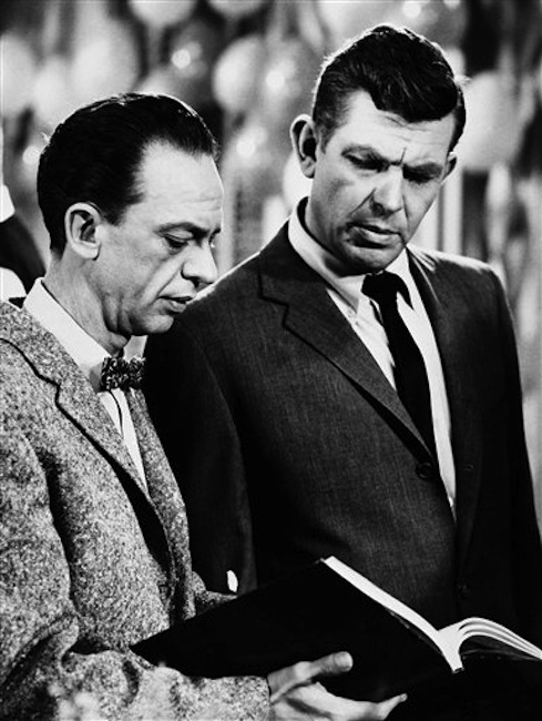 """This Jan. 24, 1963 file photo shows actors Andy Griffith as Sheriff Andy Taylor, right, and Don Knotts as Deputy Barney Fife, in a scene from the """"The Andy Griffith Show."""" Griffith, whose homespun mix of humor and wisdom made """"The Andy Griffith Show"""" an enduring TV favorite, died Tuesday, July 3, 2012 in Manteo, N.C. He was 86. (AP Photo, file) Actor;Book;Reading;Television"""