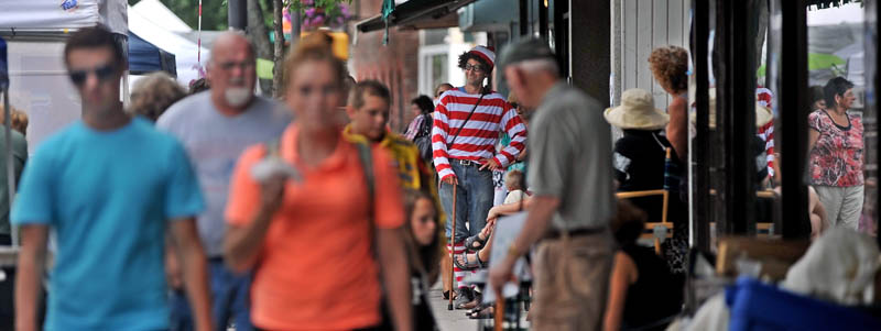 """David Gulak, center, dressed as Waldo from the popular children's book series, """"Where's Waldo?"""" is spotted on Main Street at the Waterville Intown Arts Festival on Saturday."""