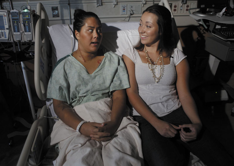Best friends Allie Young, 19, left, and Stephanie Davies, 21, sit in a room at the University of Colorado Hospital in Aurora, Colo., on Monday. Three hospitals said on Wednesday they will limit or eliminate medical bills for the victims.