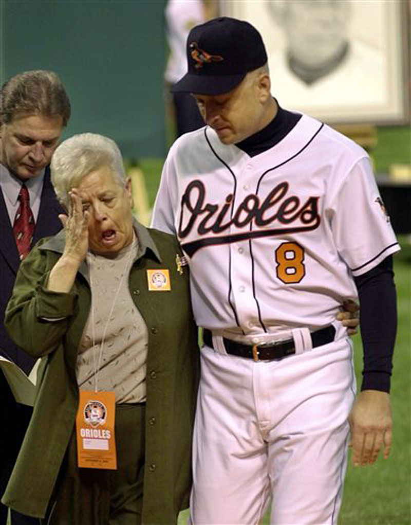 This Oct. 6, 2001 file photo shows Cal Ripken escorting his mother, Vi, from the field, after throwing out the ceremonial first pitch before Cal's final game, at Oriole Park in Baltimore. Police say Cal Ripken Jr.'s mother is safe after an armed man abducted her from her home northeast of Baltimore. Aberdeen police say 74-year-old Vi Ripken was kidnapped between 7 a.m. and 8 a.m. Tuesday, July 24, 2012, by a man who forced her into her car. (AP Photo/Nick Wass)