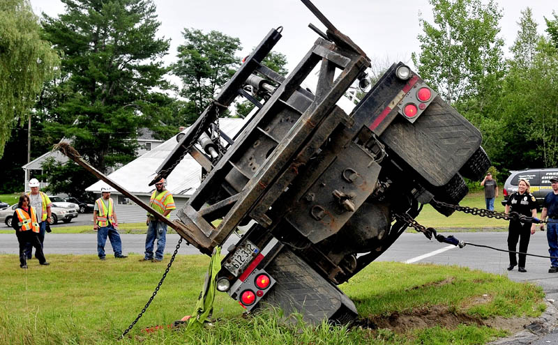 Fairfield police officer Shanna Blodgett, right, and Maine Department of Transportation employees watch as a tow truck pulls a truck upright after it collided with another vehicle at the intersection of U.S. Route 201 and 23 on Thursday, injuring two occupants. The intersection has been the site of numerous serious and fatal accidents.