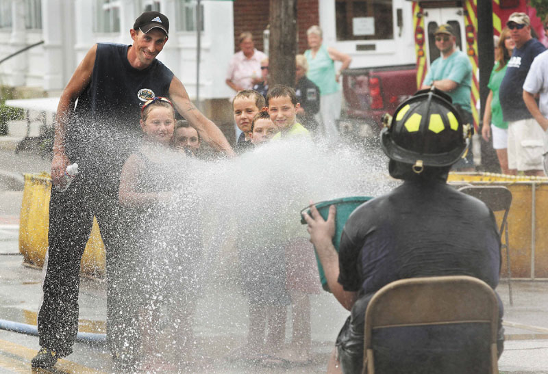 Richmond Firefighter Jason Gilpatric, left, helps some area youngsters spray a hose at firefighter Michael Baglieri, right, as he tries to a bucket at the Fireman's Muster event on Saturday at Richmond Days.