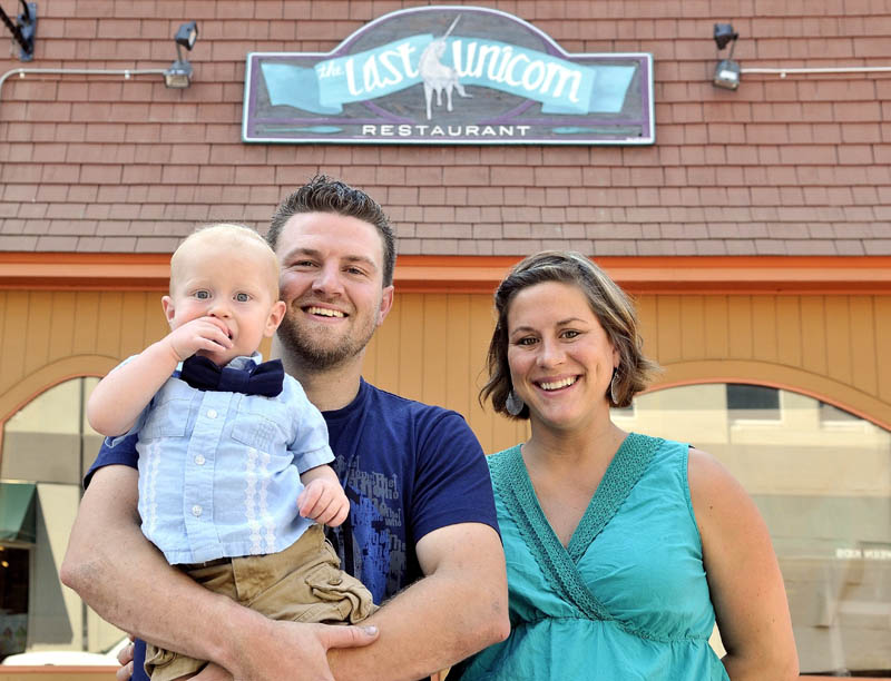 FAMILY BUSINESS: Fred and Amy Ouellette with their son Fred, Jr., stand outside the Last Unicorn in Waterville on Thursday. The Ouellettes plan to open the doors at The Last Unicorn for business in September.