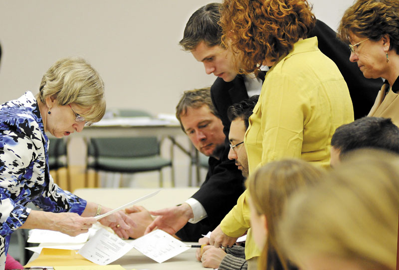 Deputy Secretary of State Julie Flynn, left, examines a ballot Monday during a recount in Augusta for House District 45. Challenger Brian Jones, D-Freedom, defeated Rep. Ryan Harmon, R-Palermo.