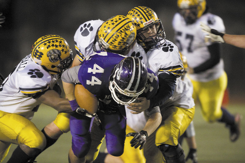 HANG ON: Mt. Blue defenders drag down Marshwood running back Brett Gerry during the second quarter of the Class B state championship game Saturday at Fitzpatrick Stadium in Portland.