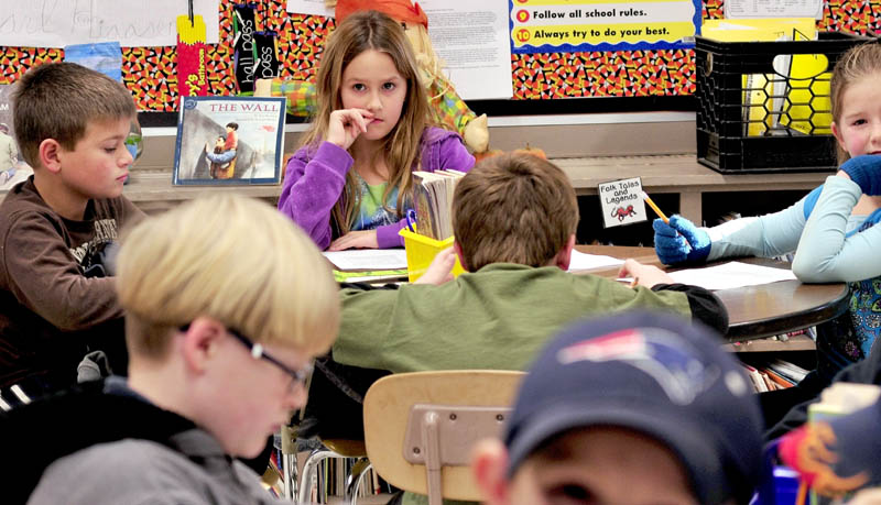 Cornville Regional Charter School student Wyntyr Herrara, center, listens with other students at a table during class in teacher Melanie Immediato's room.